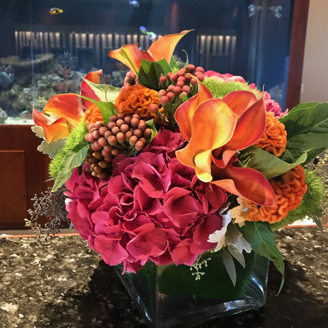 This arrangement has pink hydrangea, yellow and orange Calla lilies along with some orange coxcomb and greenery for a final touch, a unique combination of colors and design.
