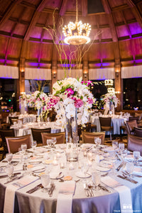 Hanging Phalaenopsis and Dendrobium orchids cascade down the tall centerpiece which also includes lavender roses, white lilies and striking curly willow shooting up the middle of the piece and towards the ceiling,