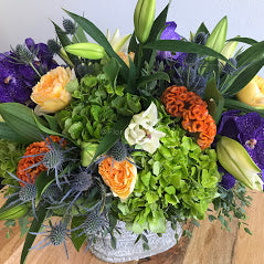 This colorful design features orange coxcomb along with blue thistle, Casablanca lilies, light yellow roses, green hydrangea, and some foliage.