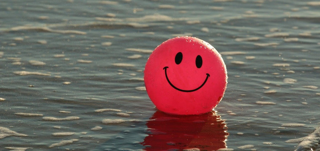 Pink ball with smile on it floating on the water.