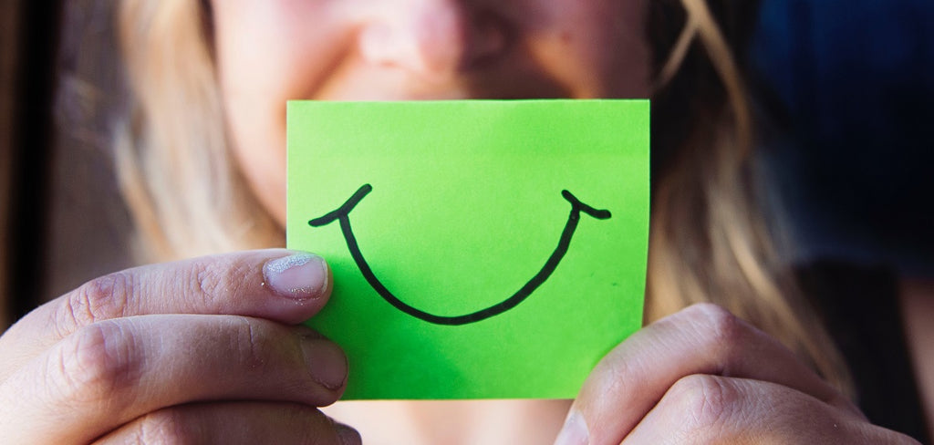 Person holding a post-it note with a smile drawn on it in front of their face.