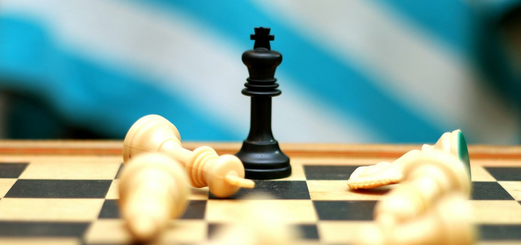 A chessboard with only the black king standing, surrounded by white pieces lying down.