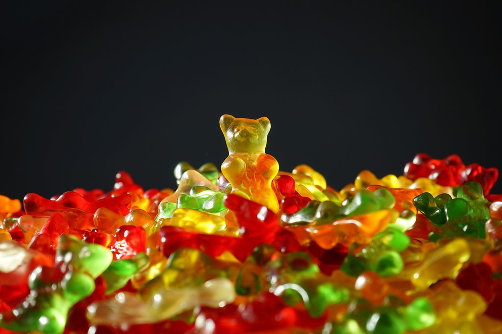 Pile of gummy bears with one gummy bear standing on top.