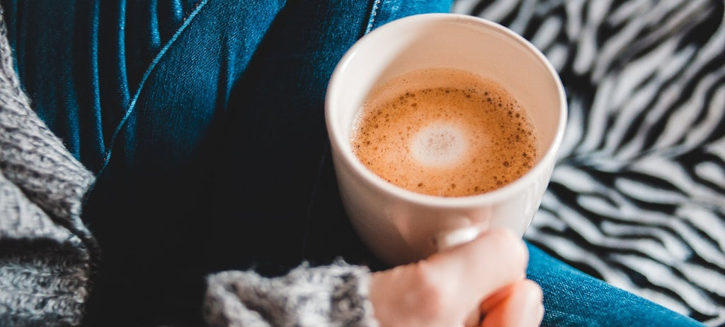 Close-up of a hand holding a cup of coffee with milk.