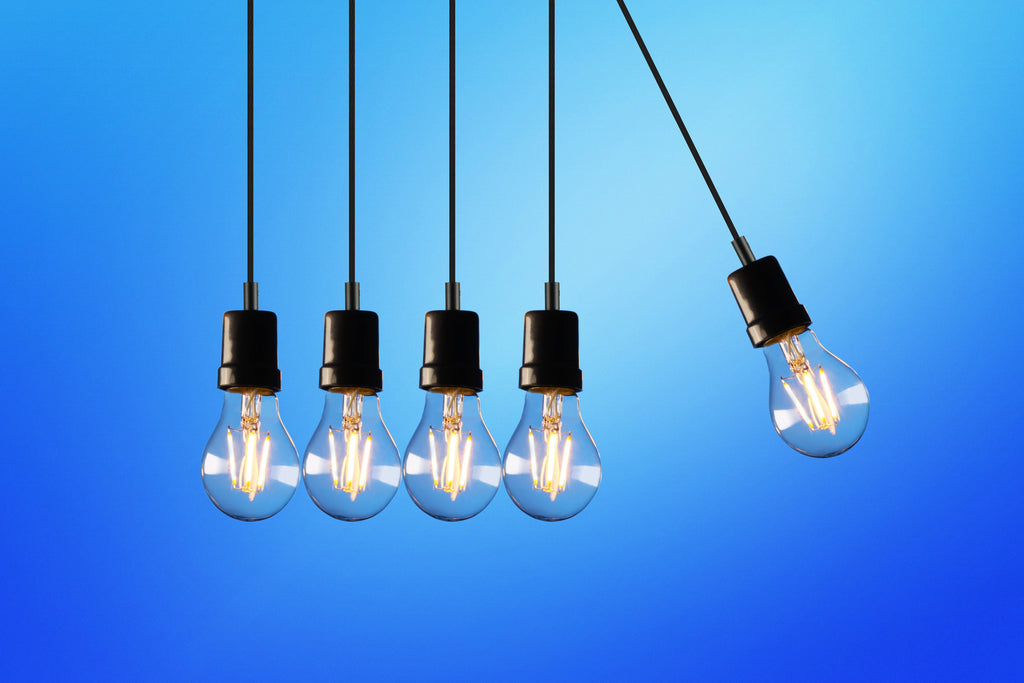 Light bulbs suspended from ceiling in front of blue wall.