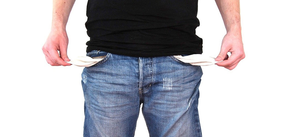 Person pulling out empty pockets from their jean shorts