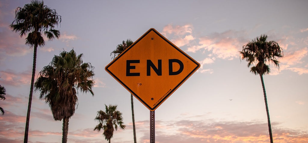 """A road sign reading """"END"""" with sky, clouds, and palm trees in the background."""