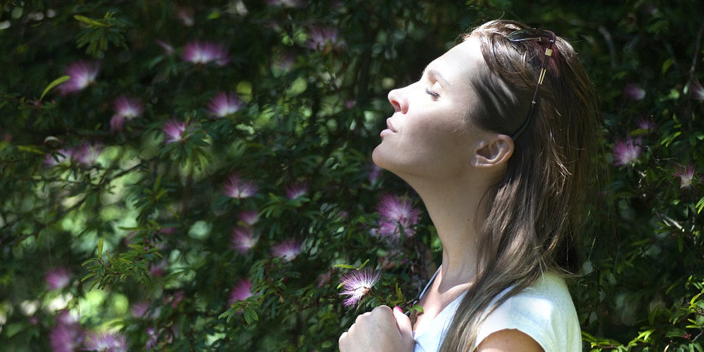 A person breathing in fresh air with plants in the background.
