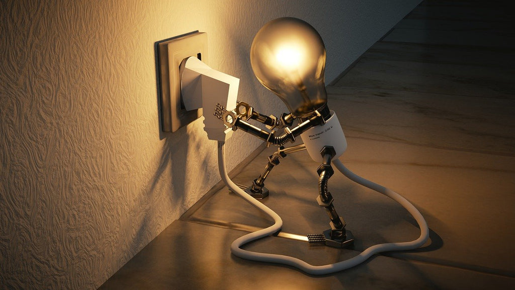 Computer generated image: light bulb standing on two legs, plugging itself into a power outlet.