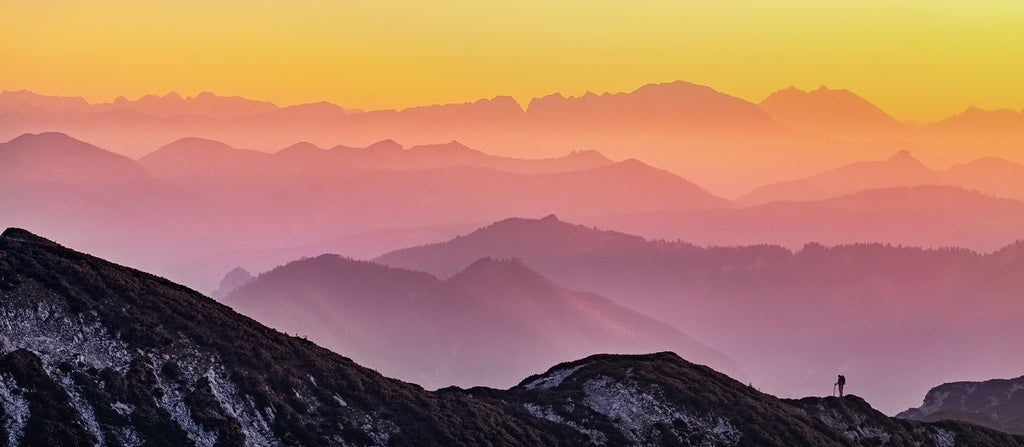 Colorful mountain vista with a distant person hiking in silhouette.