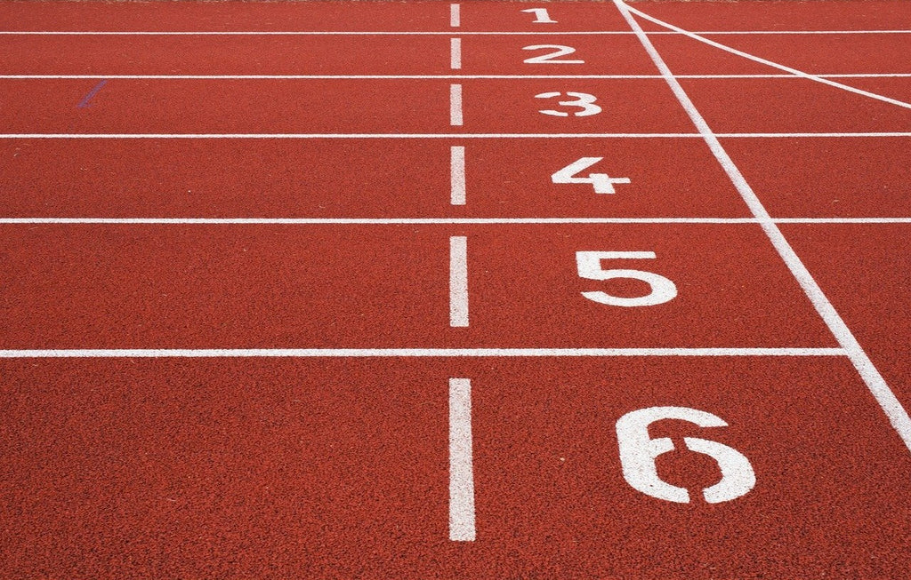 Close-up of the numbers 1-6 on a track and field racing track.