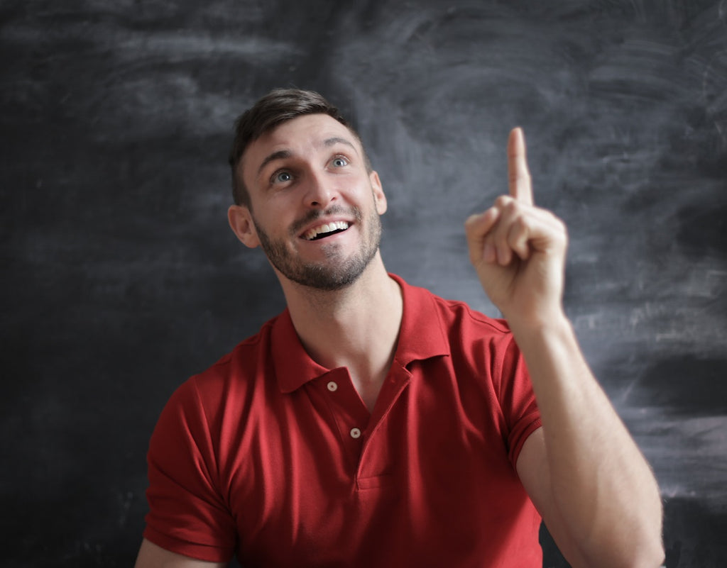 Person with mouth open, raising finger excitedly, as if they have an idea.