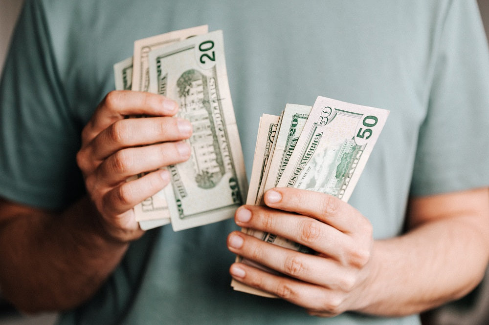 Person holding money in their hands and counting it.
