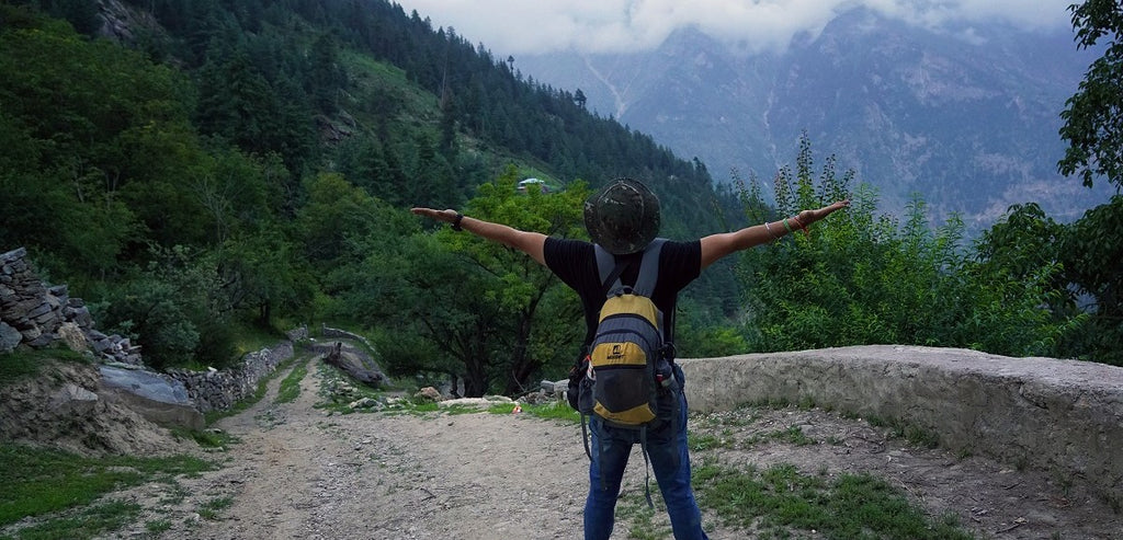 Person wearing backpack on mountain path, extending arms outwards.