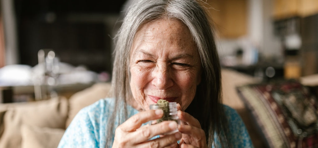A person smiling and holding a jar of cannabis flower.