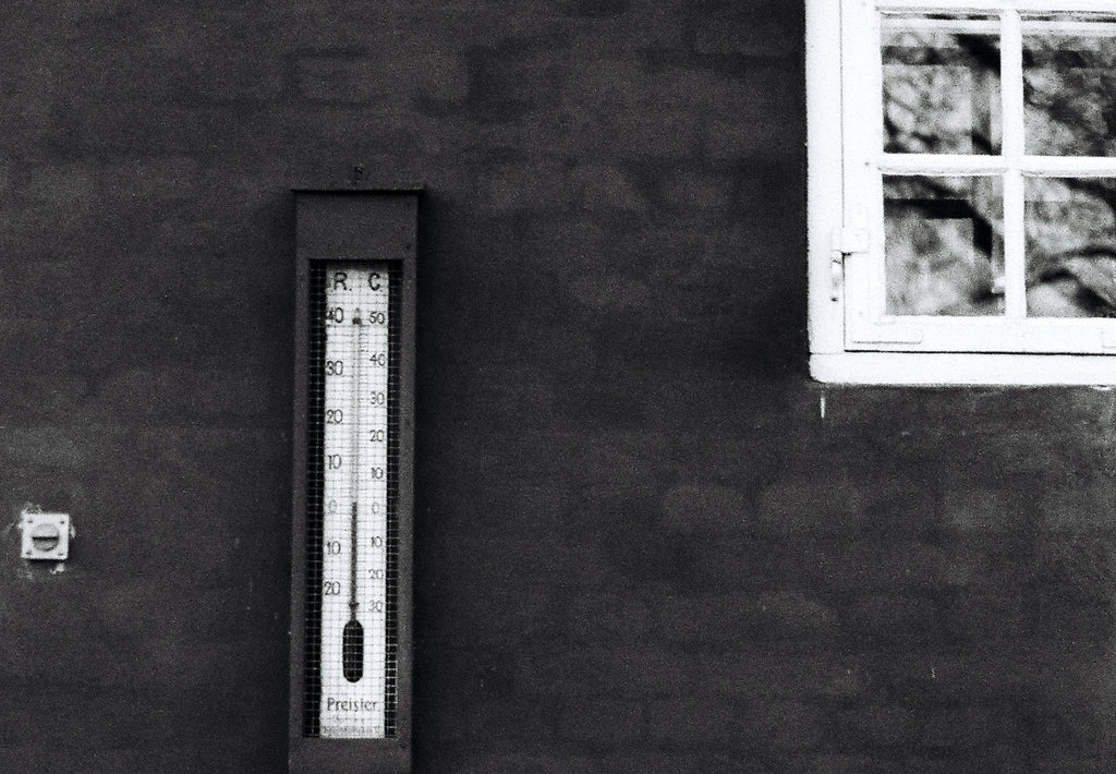 A thermometer on the outside wall of a building, beside a window.
