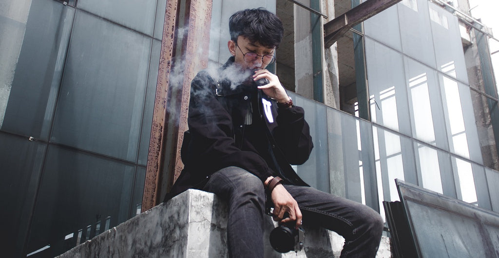 Person sitting in a construction site holding a camera and vaping.