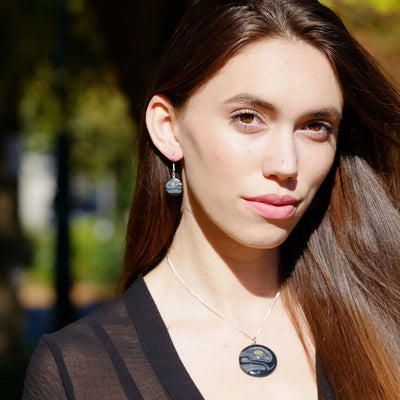 Woman wearing black argillite earrings & necklace