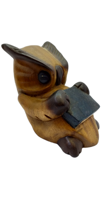 Wooden owl figurine with a book