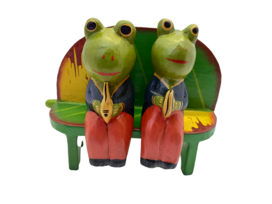 Figurine wooden frogs in love on a bench