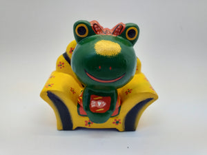 Figurine wooden frog in a chair