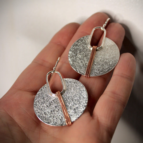 Silver circle with copper lines earrings shown on palm of hand