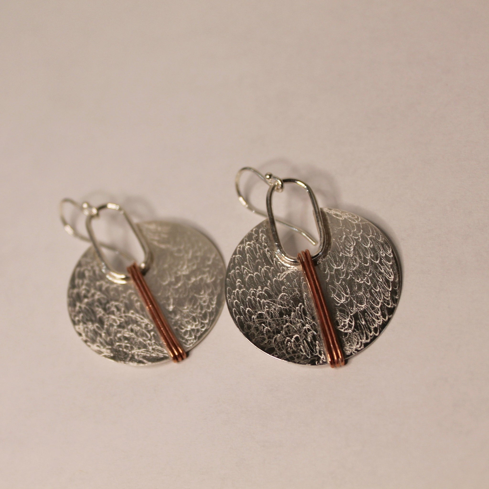 silver circle with copper lines earrings on white background