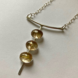Rutilated Quartz three stone necklace shown on white background