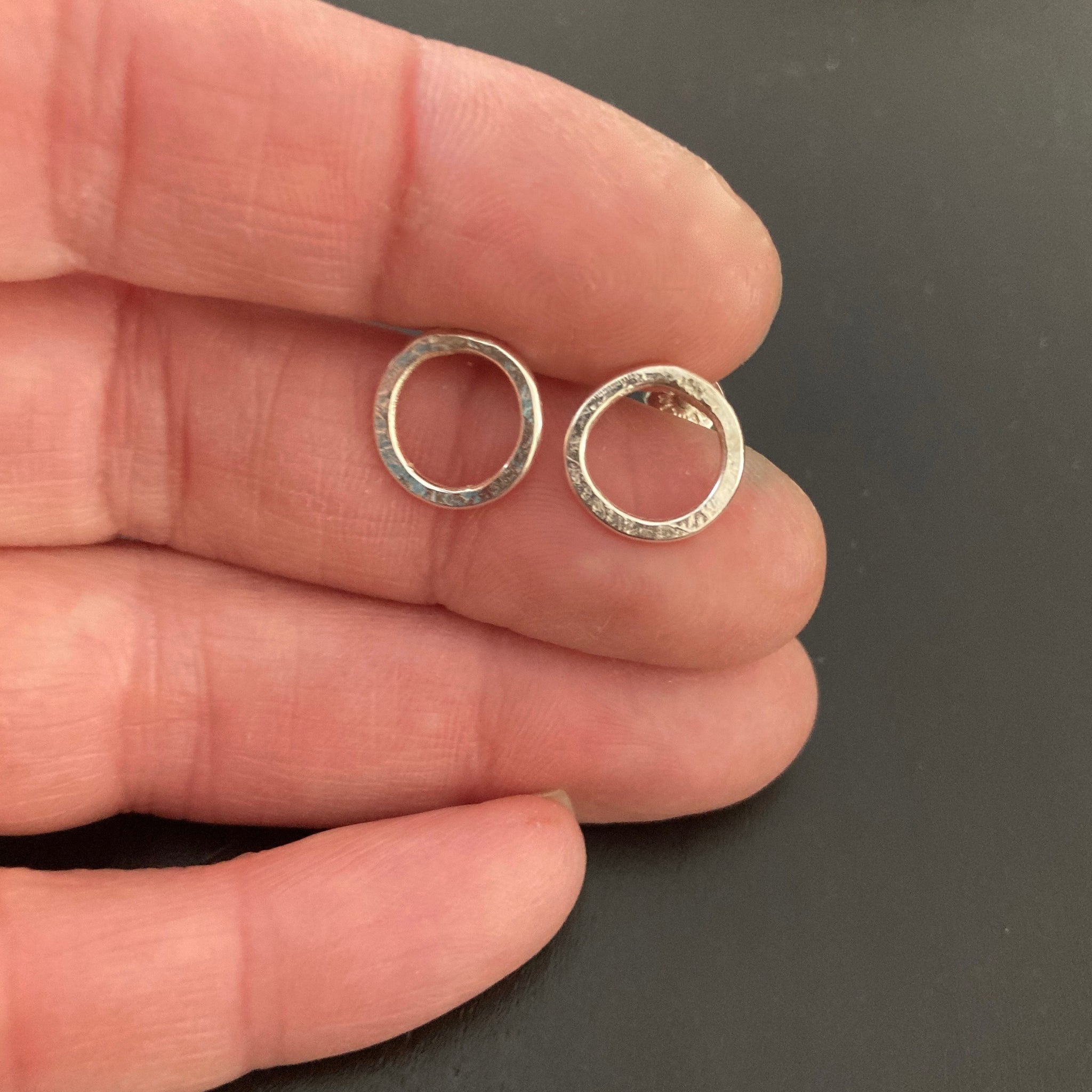 Small Silver Circle Post earrings shown in hand