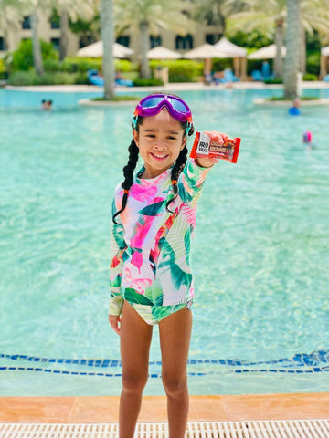 proyouth choco brownie nutritional performance bar held by child, girl next to swimming pool