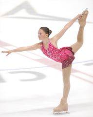 Image of cofounder of Algi, Alessandra Amato, figure skating in an ice rink wearing a pink dress. Her leg is up above her head, held in place by her hand as she glides across the surface of the ice.