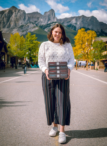 Cofounder Alessa Amato standing in the street in downtown Canmore in front of mountains, holding 4 boxes of Algi's IMPACT Bars
