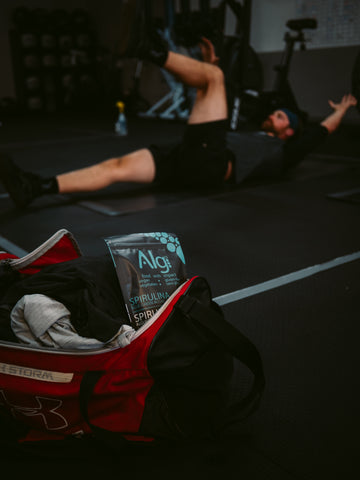 Man at cross fit gym doing core exercises during a workout. In front of him is a vegan protein powder, spirulina algae