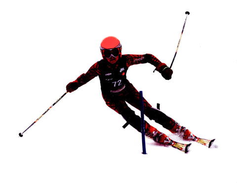 Cofounder Devon Hawkins is downhill ski racing down a hill in a mountain in Banff Alberta Canada. He is wearing a dark ski suit and skiing through a gate as he races down the hill