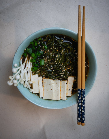 Blue-green bowl of delicious spirulina algae ramen noodles make with vegetable broth, oyster mushrooms, and tofu, topped with sesame seeds and green onions. Placed on top of the blue-green bowl is a pair of chopsticks resting together.