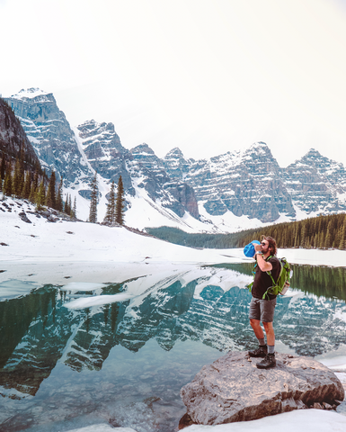 Man hiking a trail in Canmore and Banff Alberta Canada. He is standing on the edge of a lake with snow capped mountains behind him.