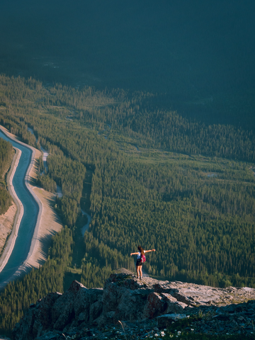 Girl hiking in Canmore and Banff Alberta Canada. Girl is standing on a rocky outcropping overlooking a valley filled with trees and wildlife.