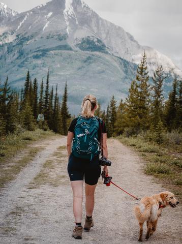 Girl hiking at the base of a mountain with a packed backpack and her dog in Canmore and Banff Alberta Canada