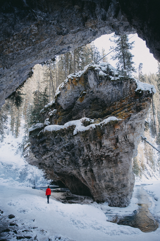 Man in red winter jacket standing at base of giant rock formation in Johnston Canyon Trail. Snow covers the mountains, cliff walls, and trees