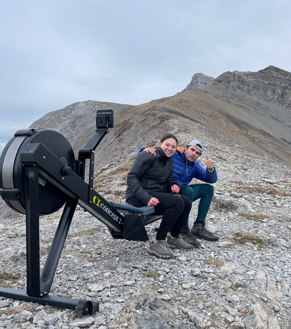 Devon and Alessa sitting on an erg rowing exercise machine on top of Ha Ling mountain in Canmore Alberta