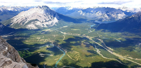 View from the summit of Mount Rundle overlooking the valley of green trees, and blue rivers. A chain of snow capped mountains are seen in the distance