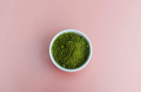 White bowl of blue-green spirulina algae powder, vegan powder, sitting on a pale pink surface. This vegan protein powder is a healthy gluten free snack that can be made into energy date bars.