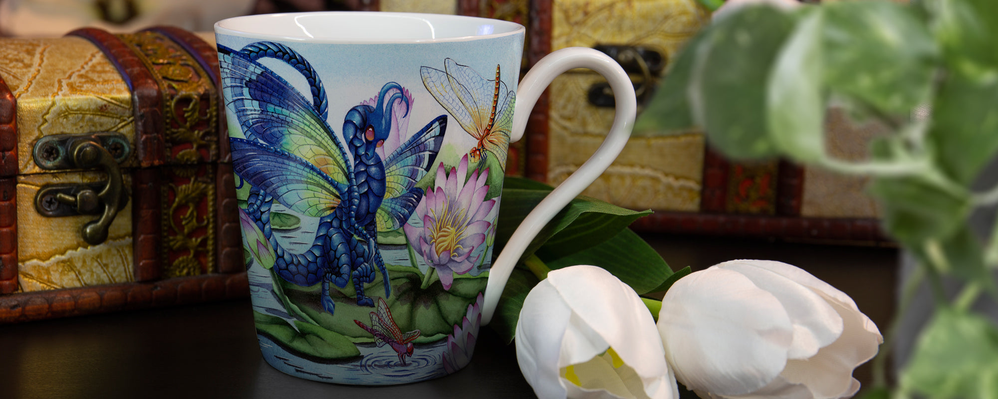 dragon mug on a table with flowers and treasure boxes