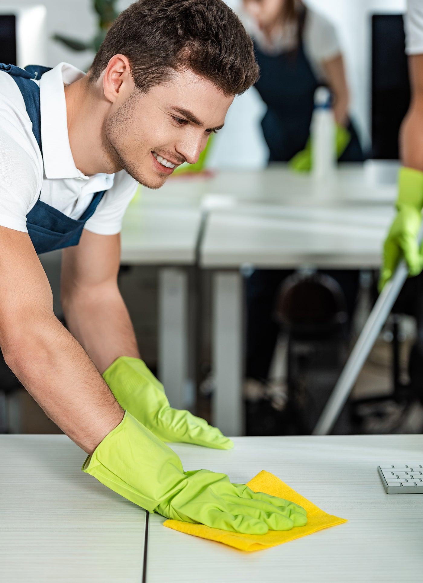 Man in gloves disinfecting desk with cloth