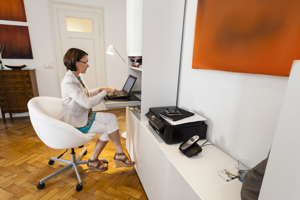 Woman working from home office using printer