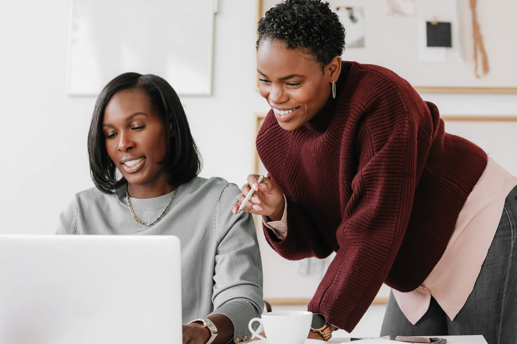 two businesswomen are happily looking at laptop