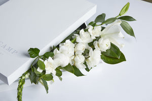 large white gift box overflowing with flowers and lots of gardenias