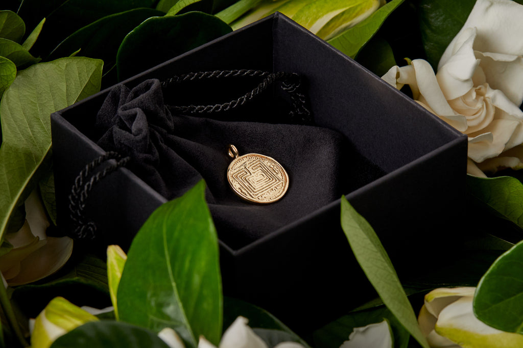 gold labyrinth pendant in black gift box with gardenias