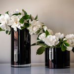 Two black vases filled with gardenias