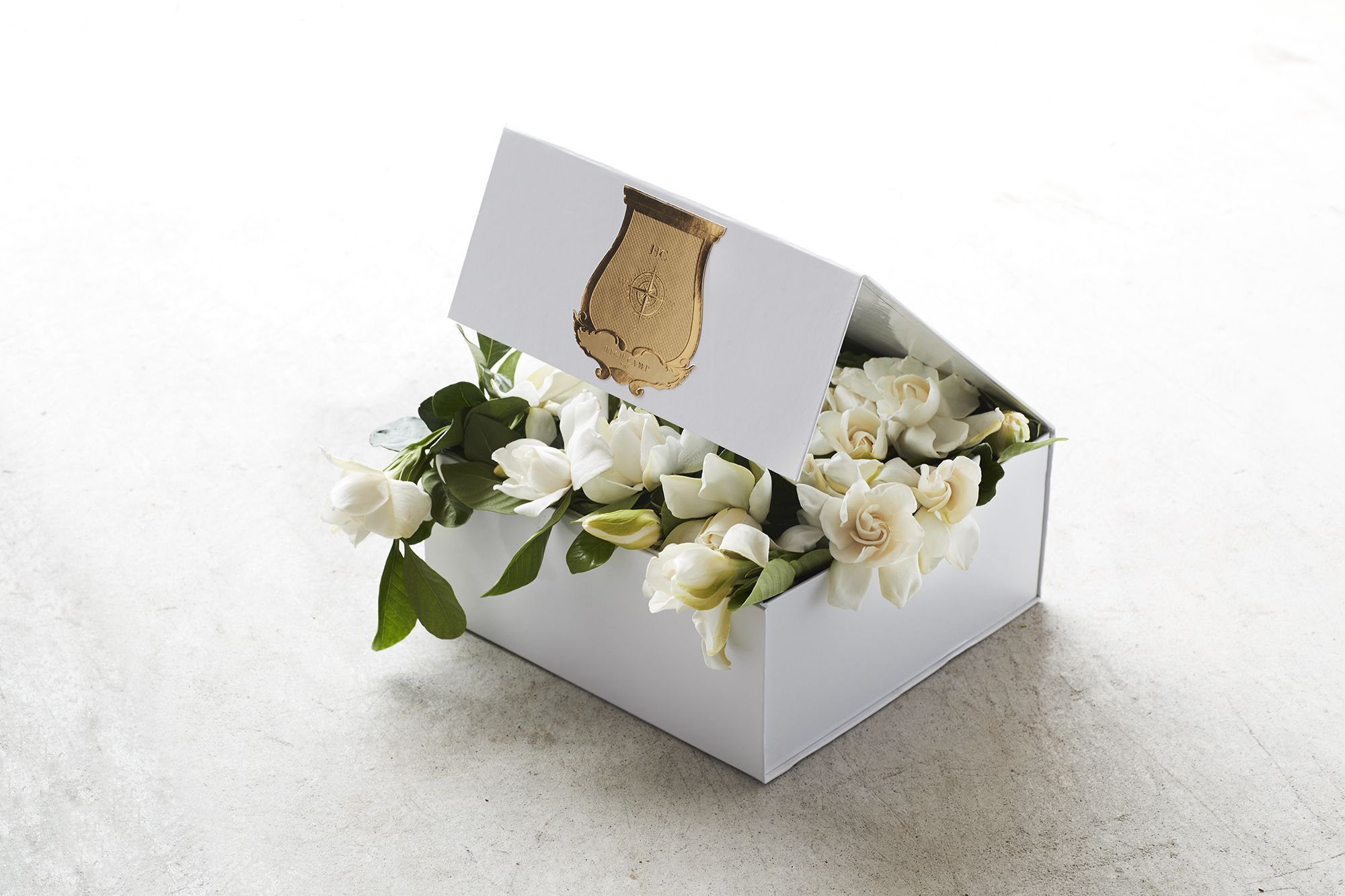 white branded gift box with gardenias overflowing
